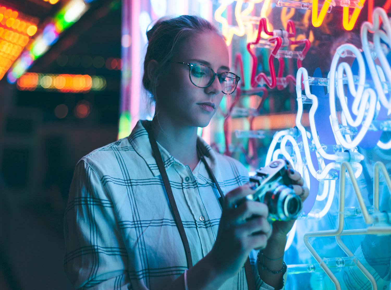 Neon Licht Fotoshooting auf dem Oktoberfest: Junge Frau vor Neonlicht mit einer Vintage Kamera auf dem Oktoberfest München