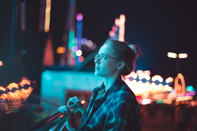 Model im Neonlicht eines Fahrgeschäftes auf der Wiesn in München