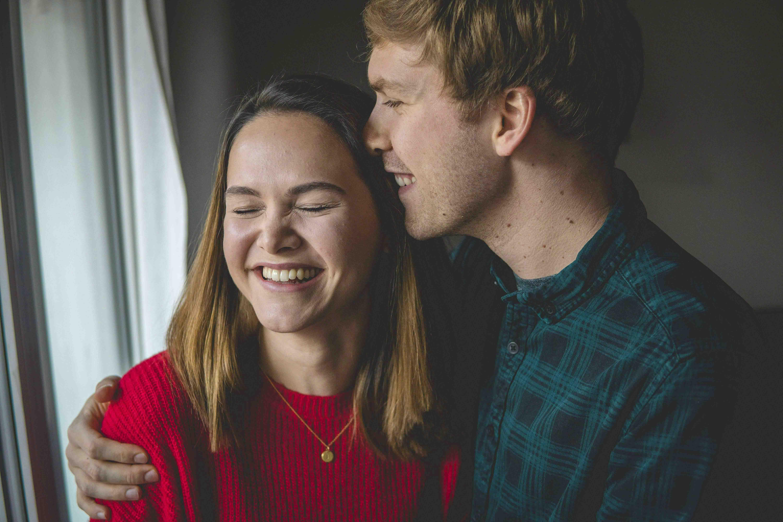 Lachendes junges Paar mit Umarmung