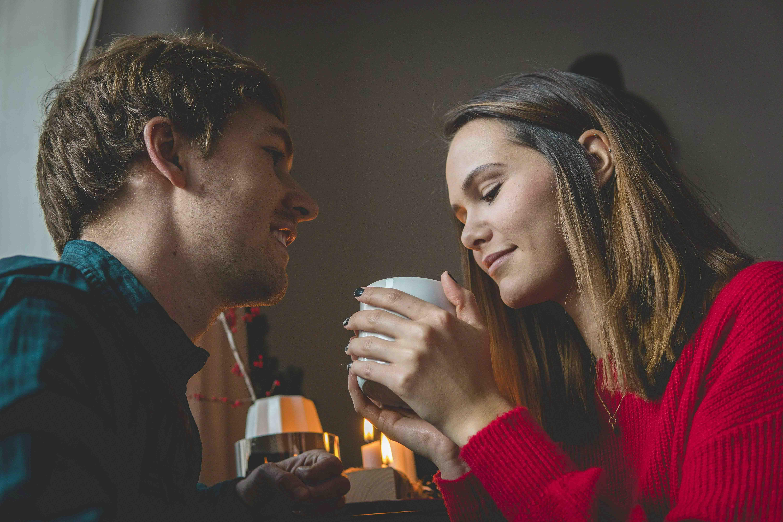 Hübsches junges Paar mit Kaffeetasse im Wohnzimmer
