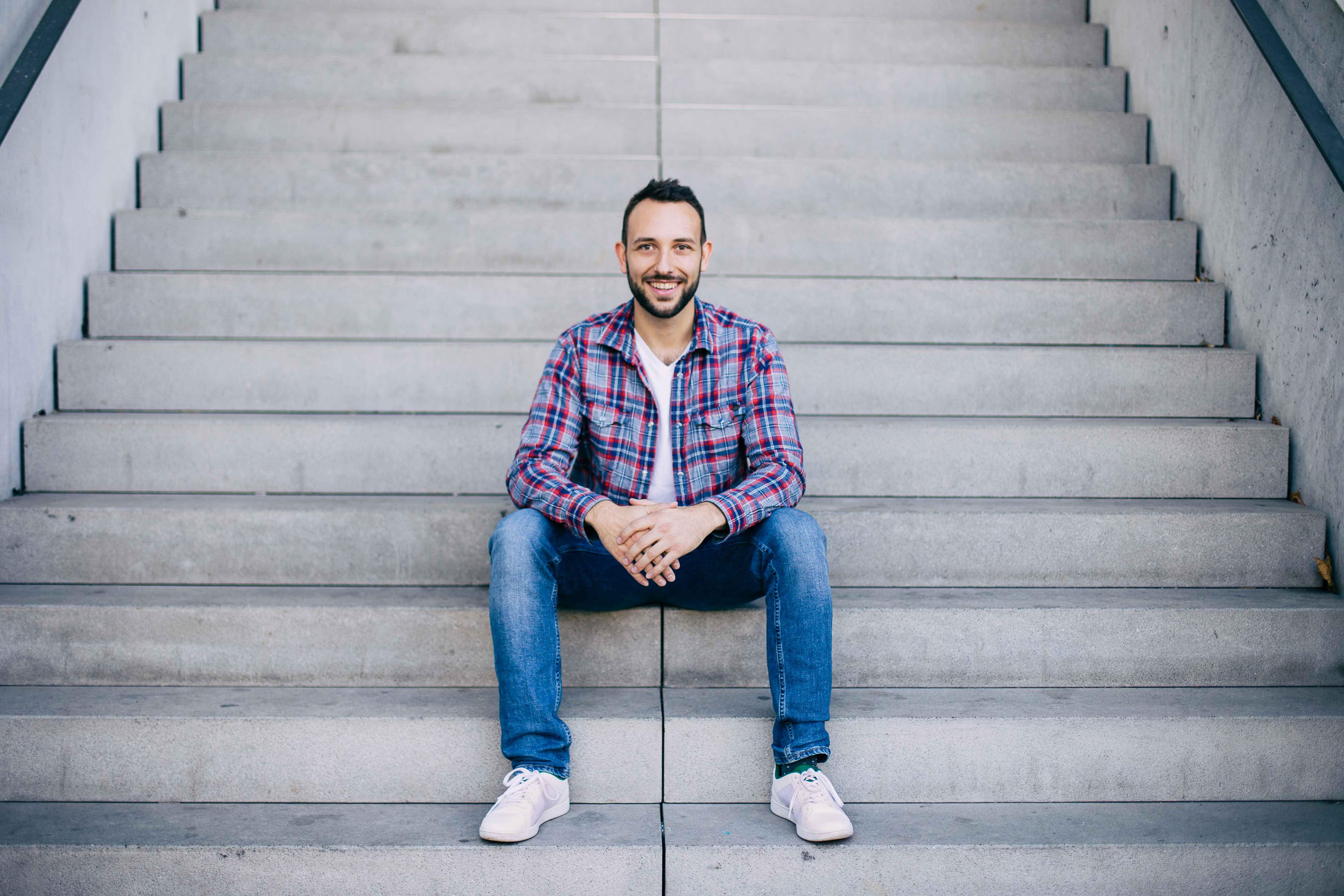 Symmetrisches Porträtfoto eines jungen Manns auf einer Treppe sitzend