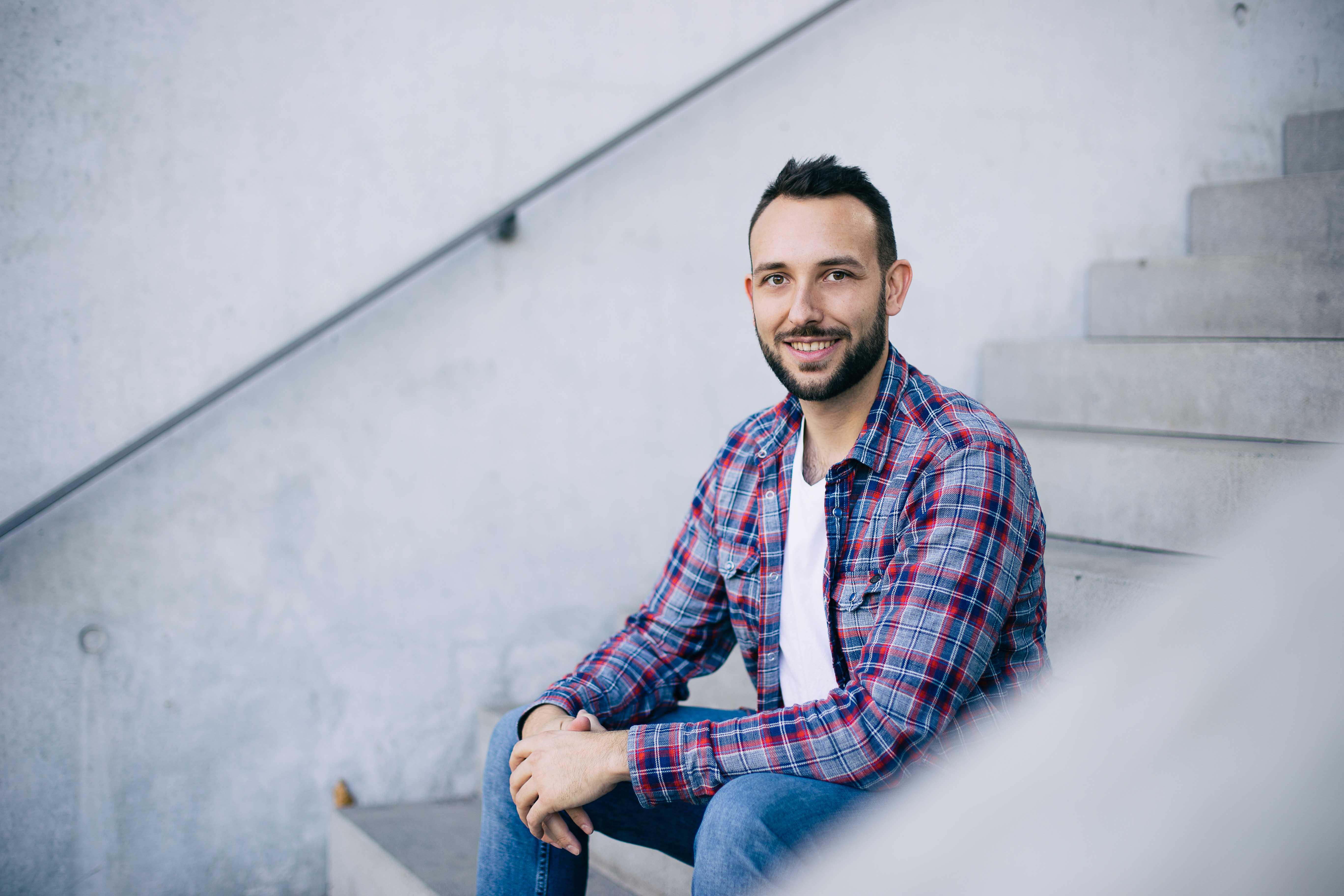 Porträtfoto eines jungen Manns auf einer Treppe sitzend