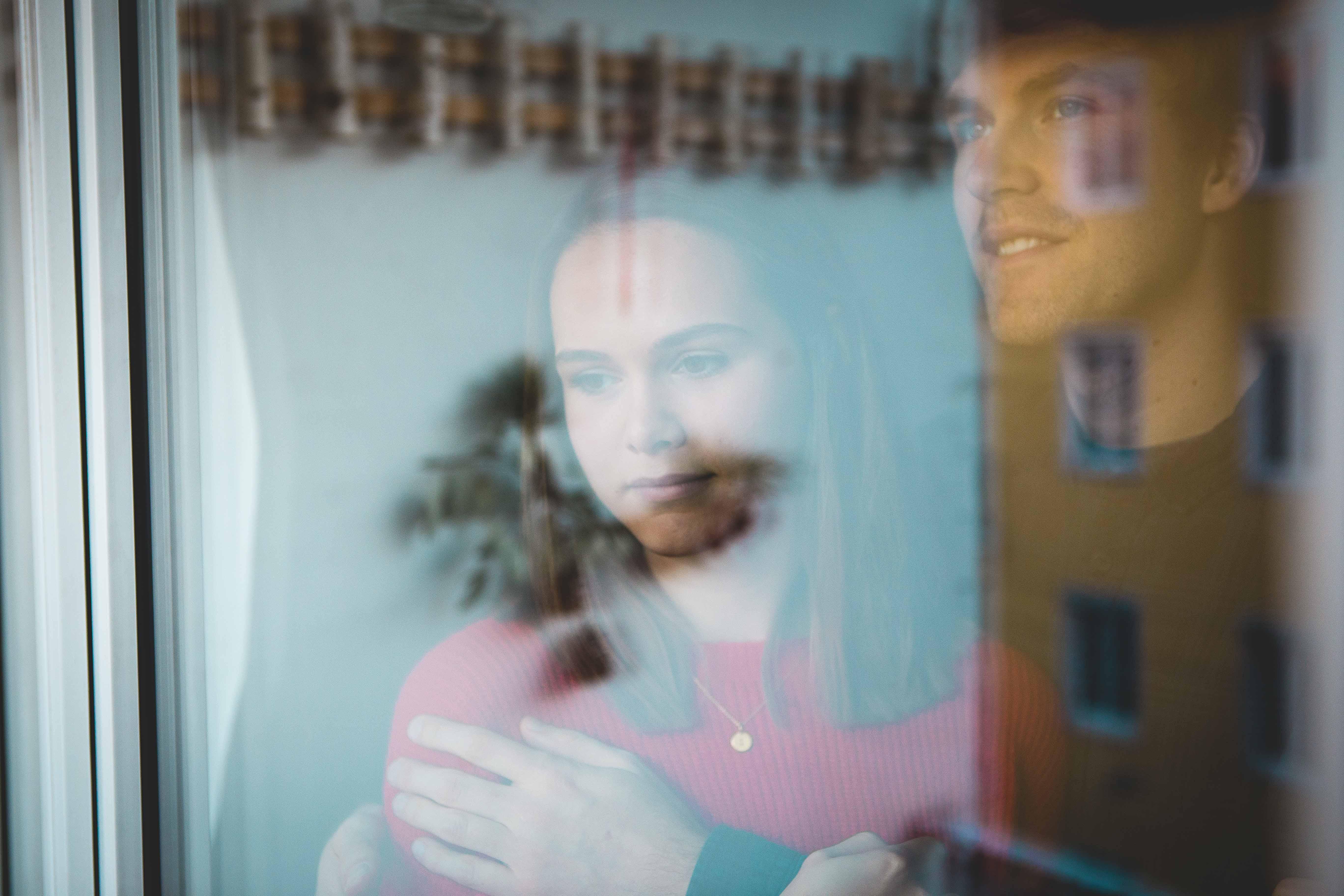 Pärchen mit verträumten Blicken am Fenster