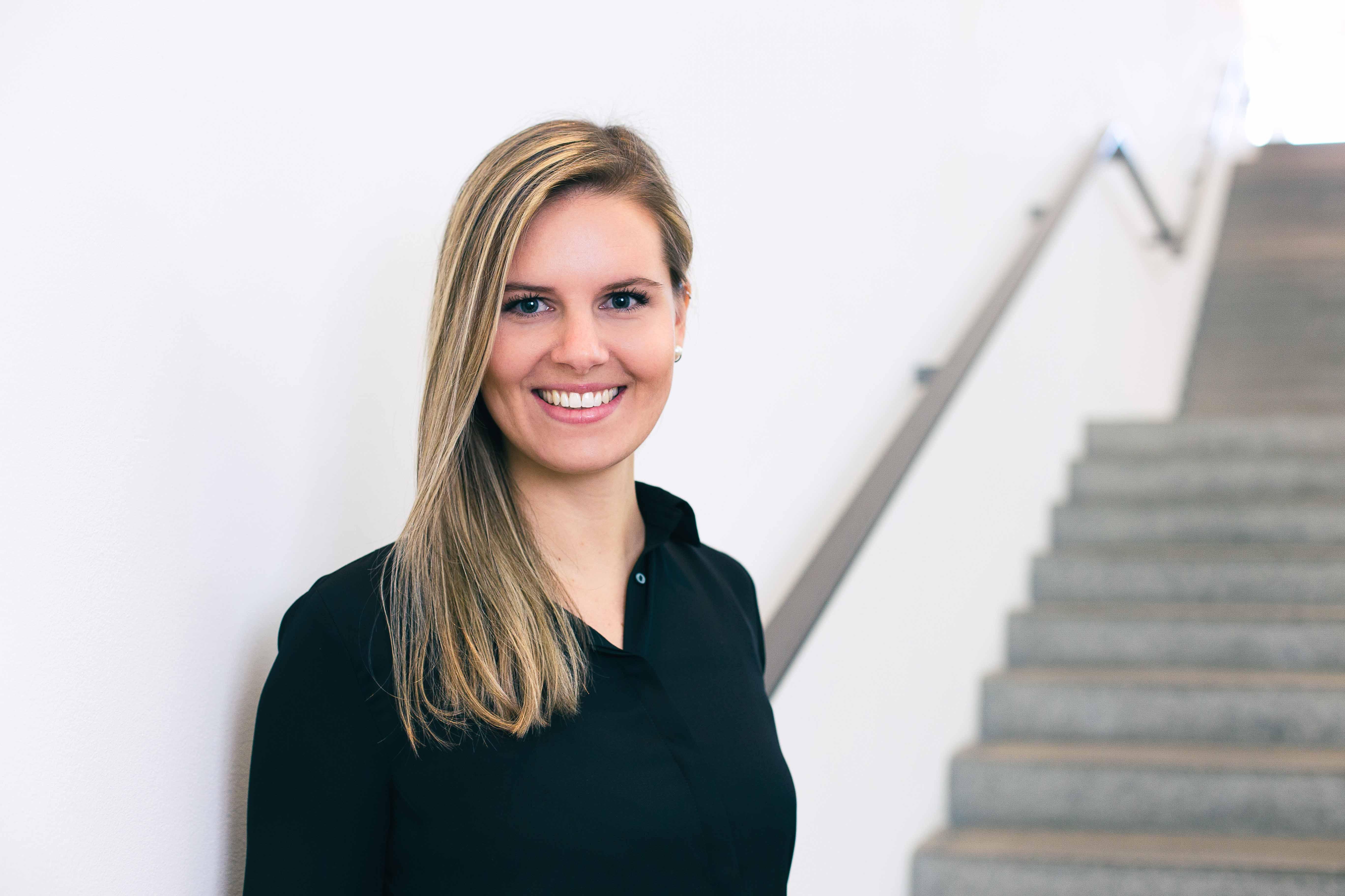 Businessfoto einer blonden Frau in schwarz vor einer Treppe