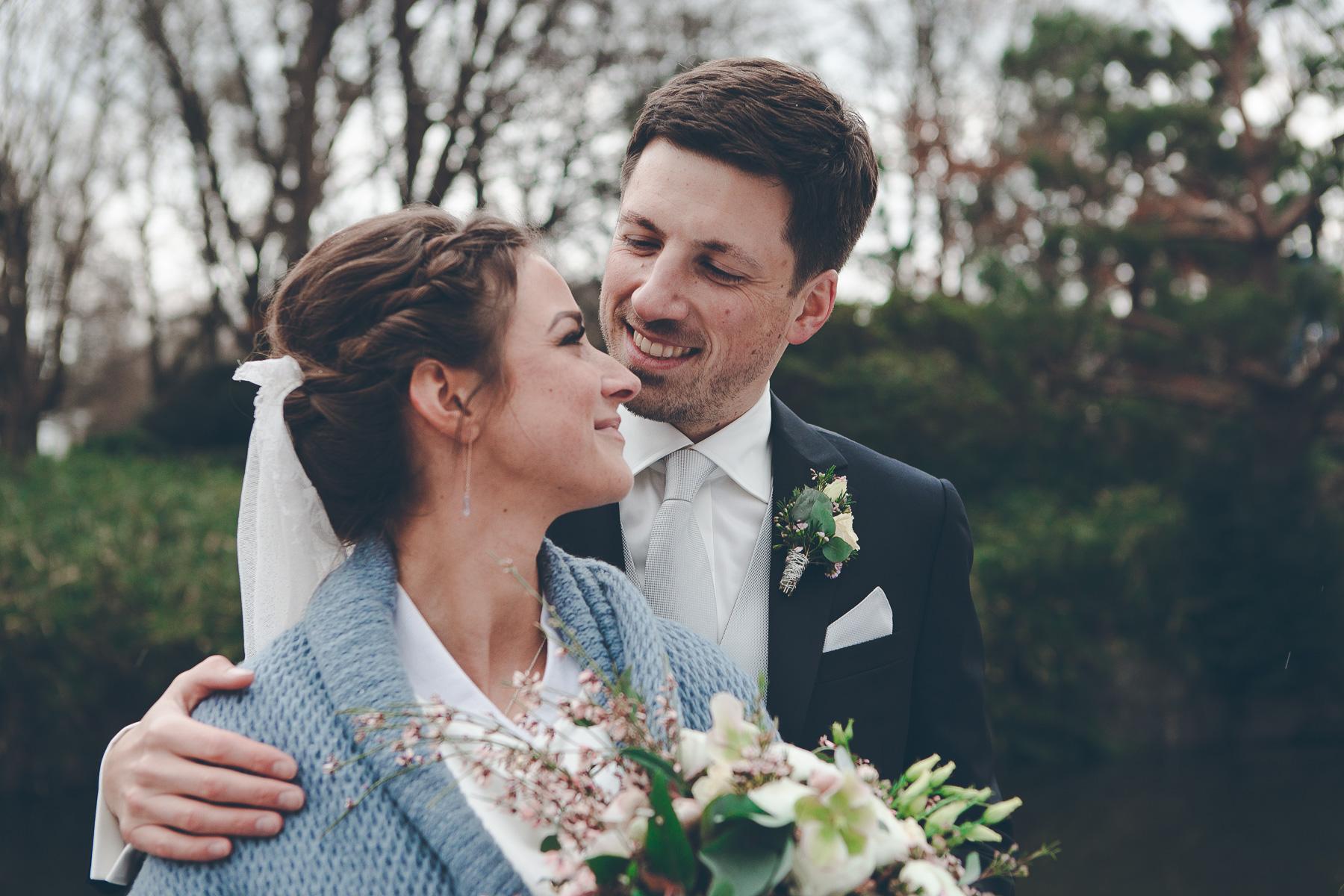 Verliebtes Hochzeitspaar beim Hochzeitsbilder machen im Park in Sendling