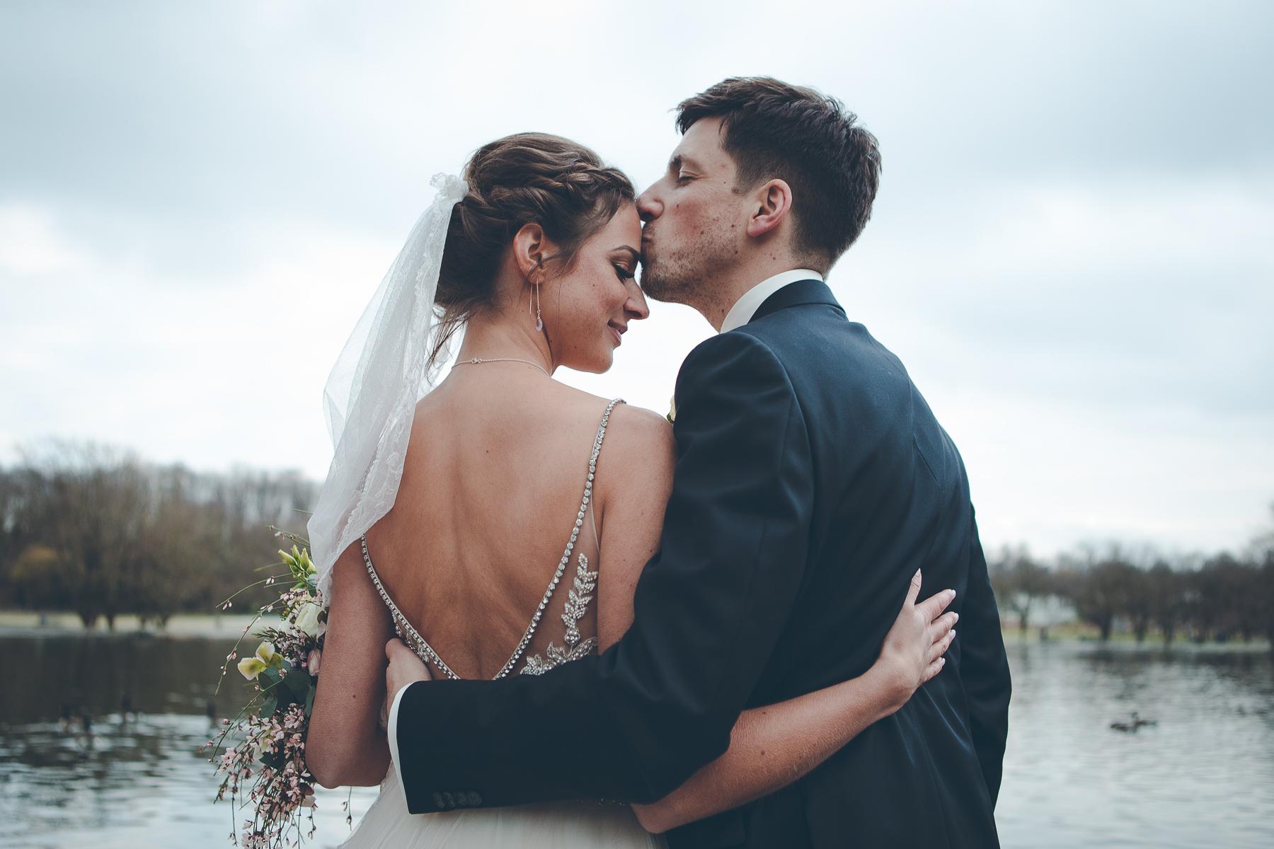 Hochzeitsbilder: Bräutigam küsst Braut auf die Stirn am See im Westpark
