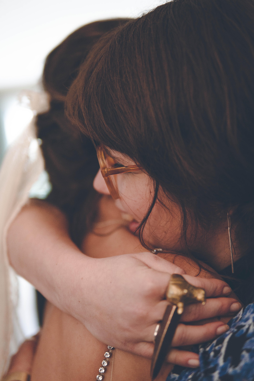 Braut und Freundin umarmen sich nach der Hochzeit