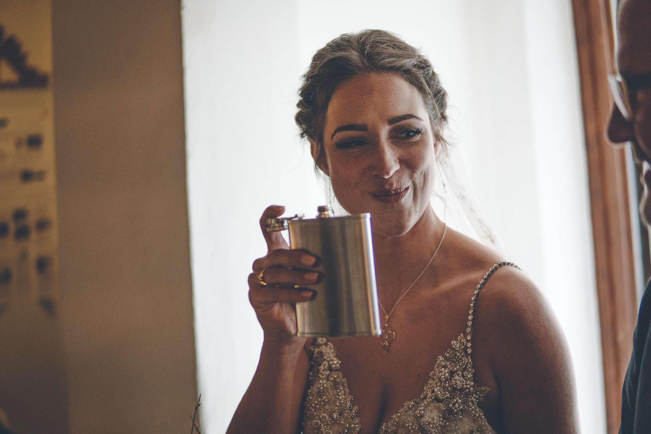 Braut vor der Hochzeit trinkt aus einem Flachmann