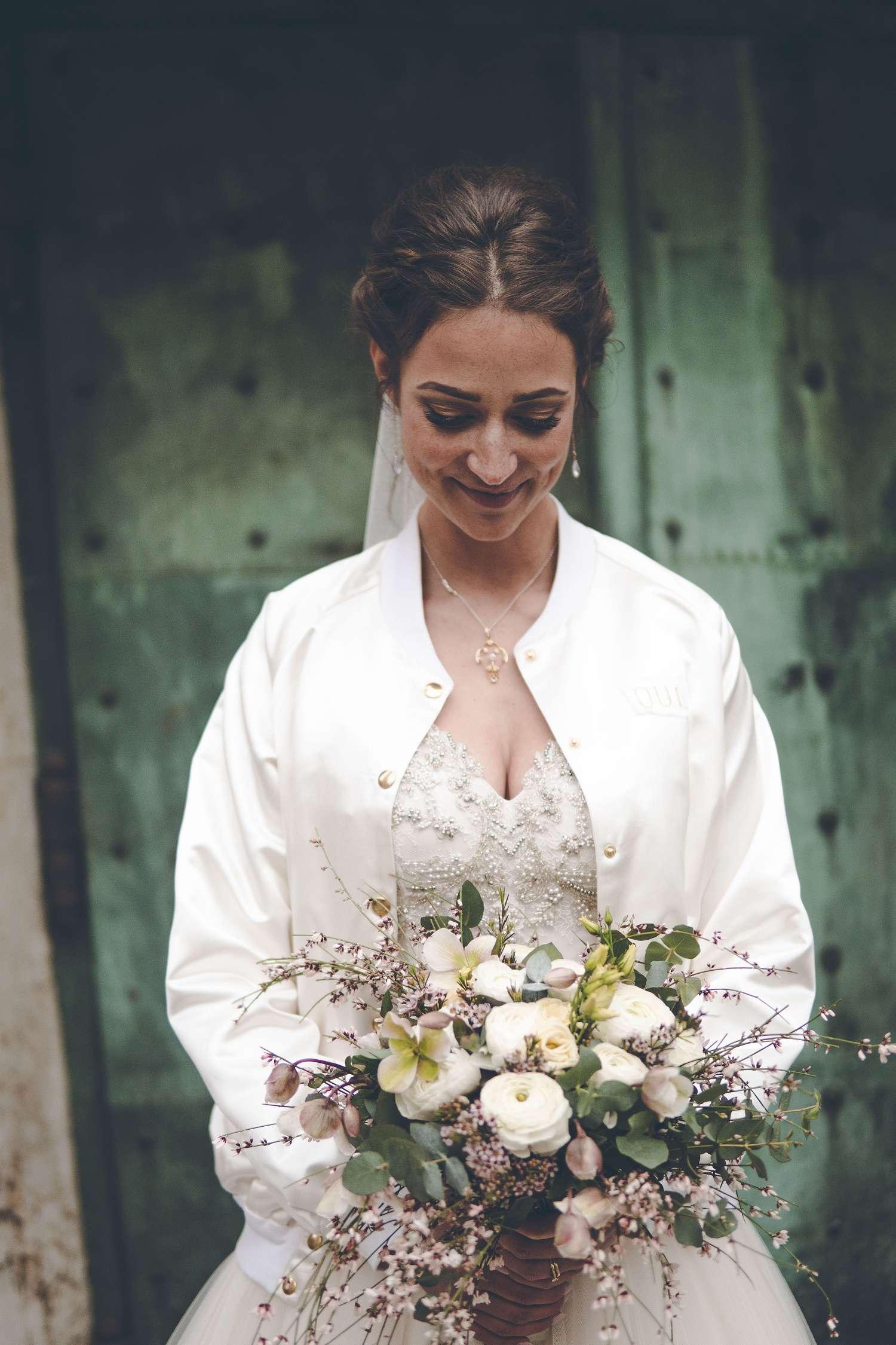 Eine hübsche Braut mit ihrem Blumenstrauß vor der Kirche