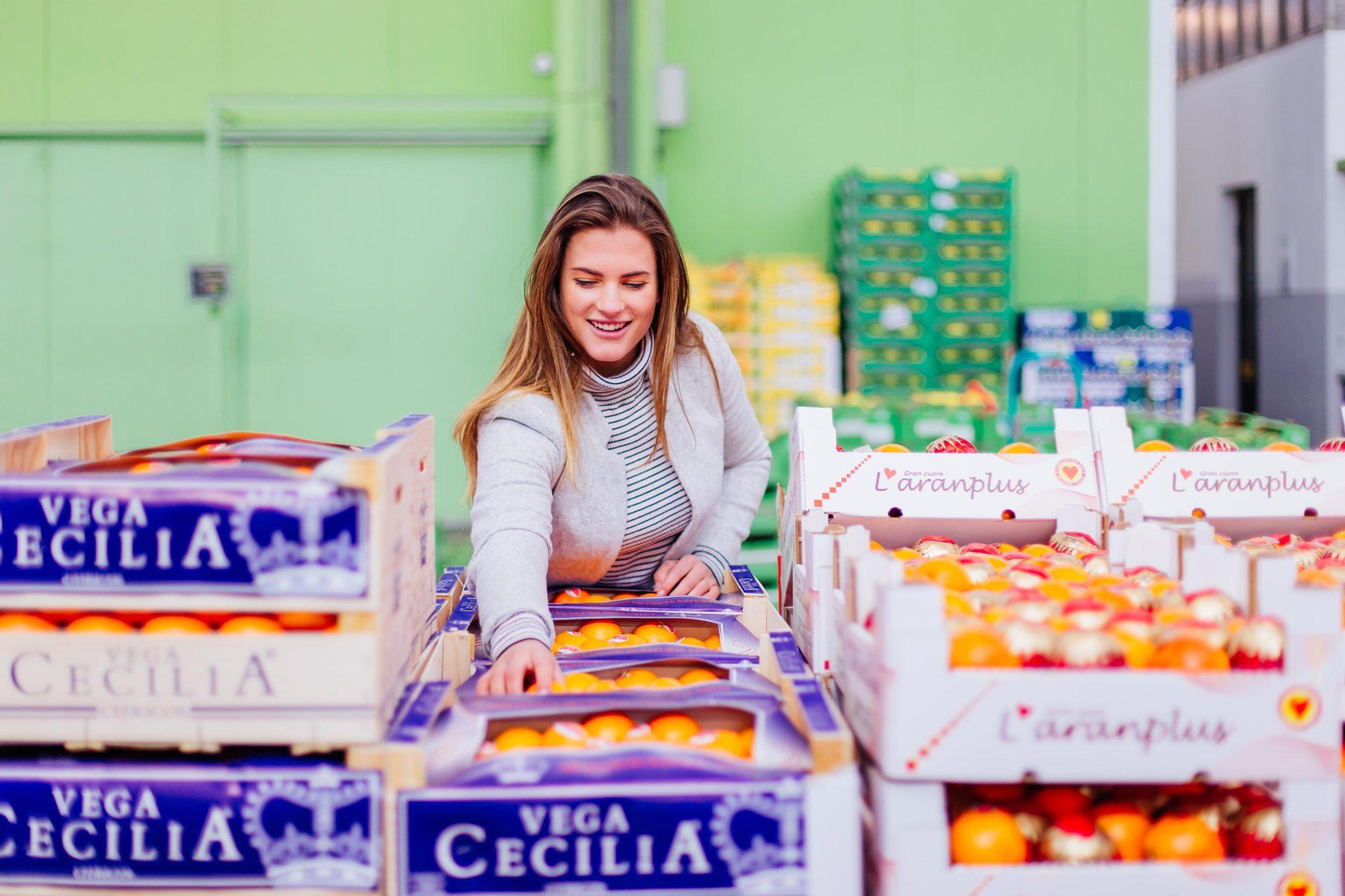 Werbefoto einer Frau beim orangen aussuchen im Großhandel