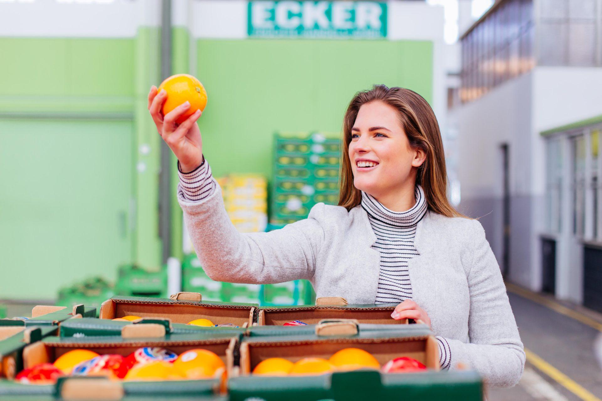 Junge Frau hält Orange hoch um sie zu begutachten