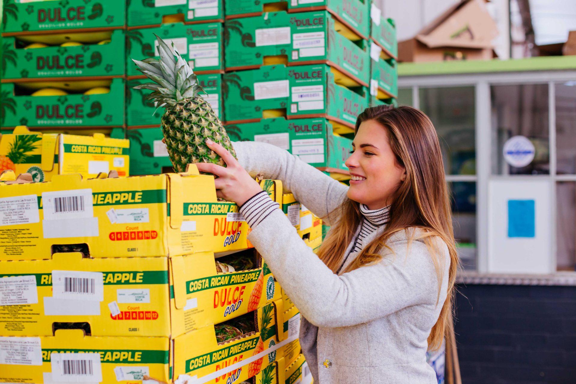 Frau beim Einkaufen mit Ananas
