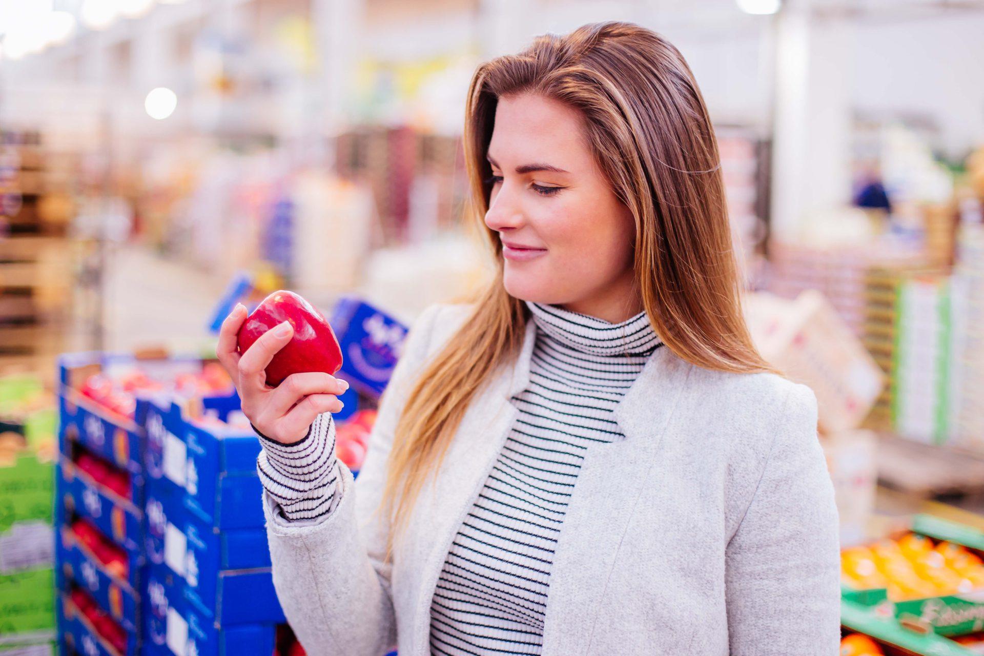 Junge Frau mit Apfel im Supermarkt