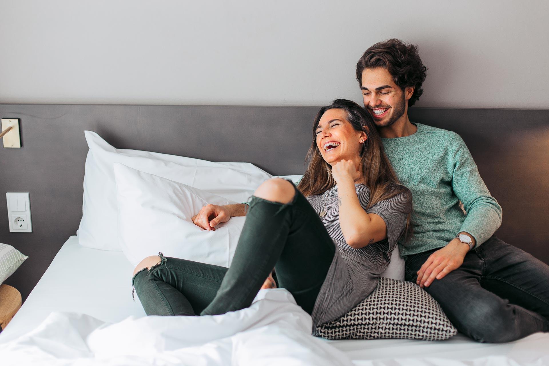Social Media Fotografie eines jungen cool angezogenen herzlich lachenden Paars auf einem Hotelbett
