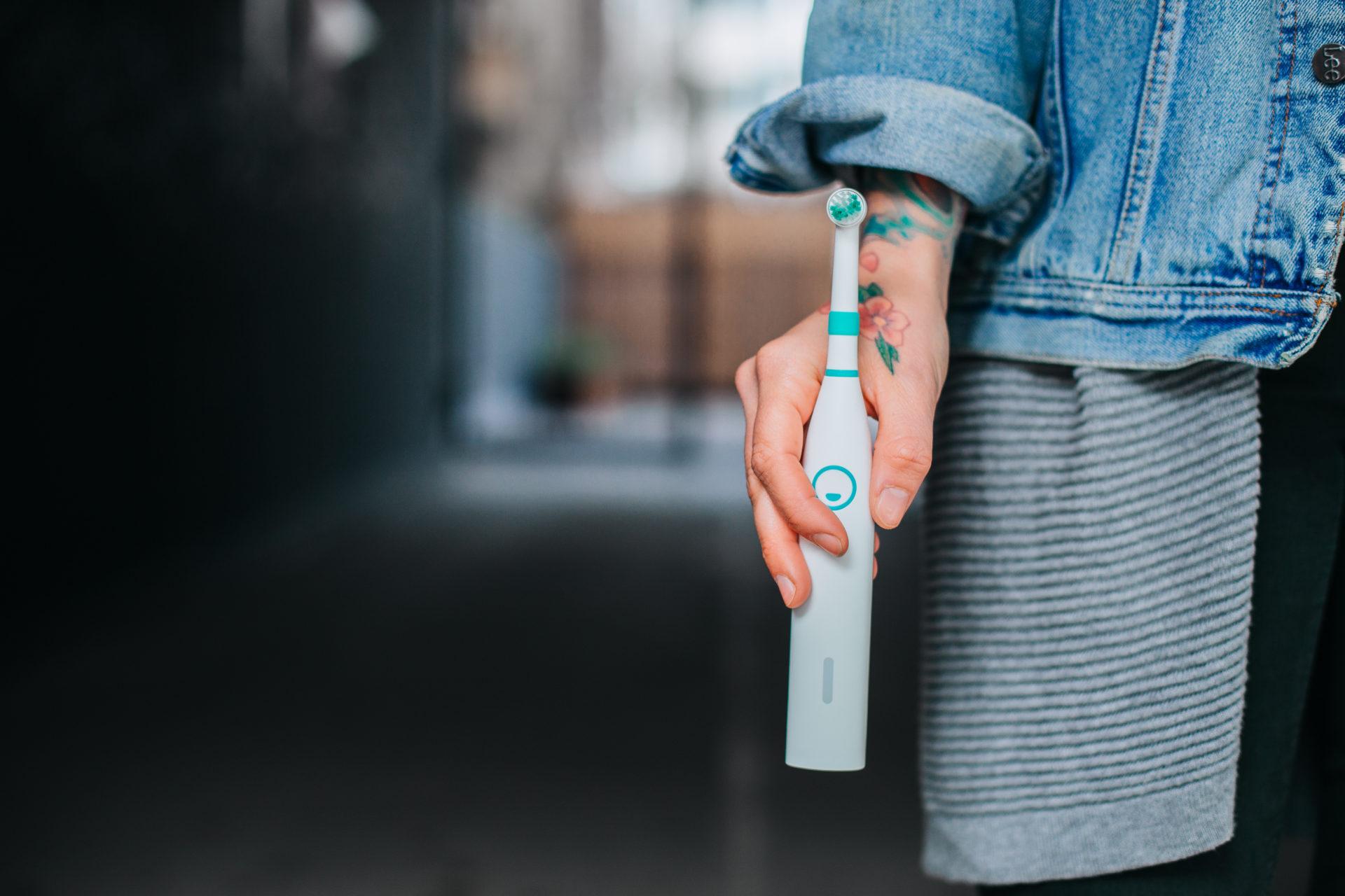 Happybrush Zahnbürste in der Hand eines Models