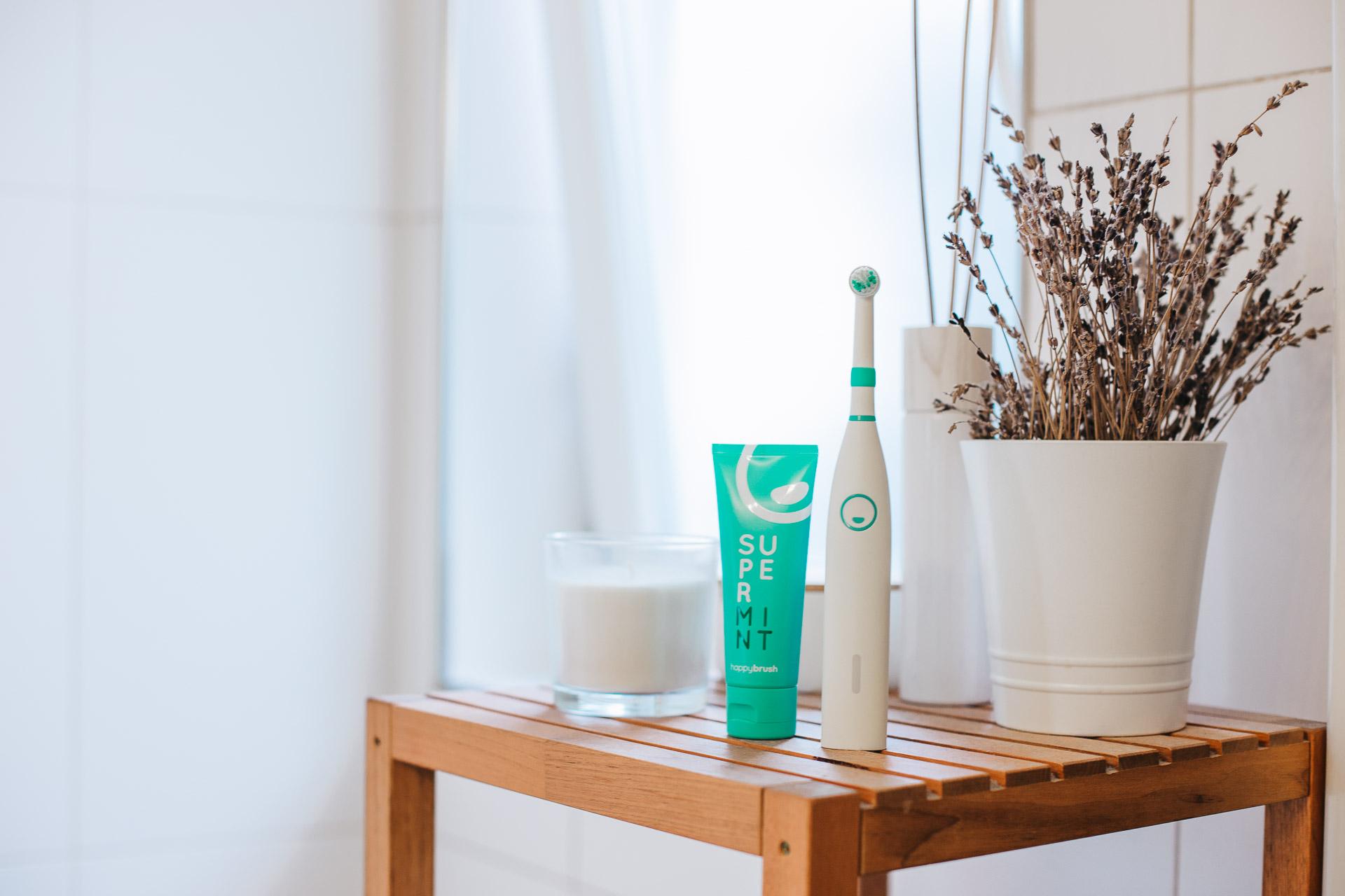 Ein Social Media Fotografie Produktfoto Stilleben mit einer Happybrush und Zahnpasta in einem hellen Bad