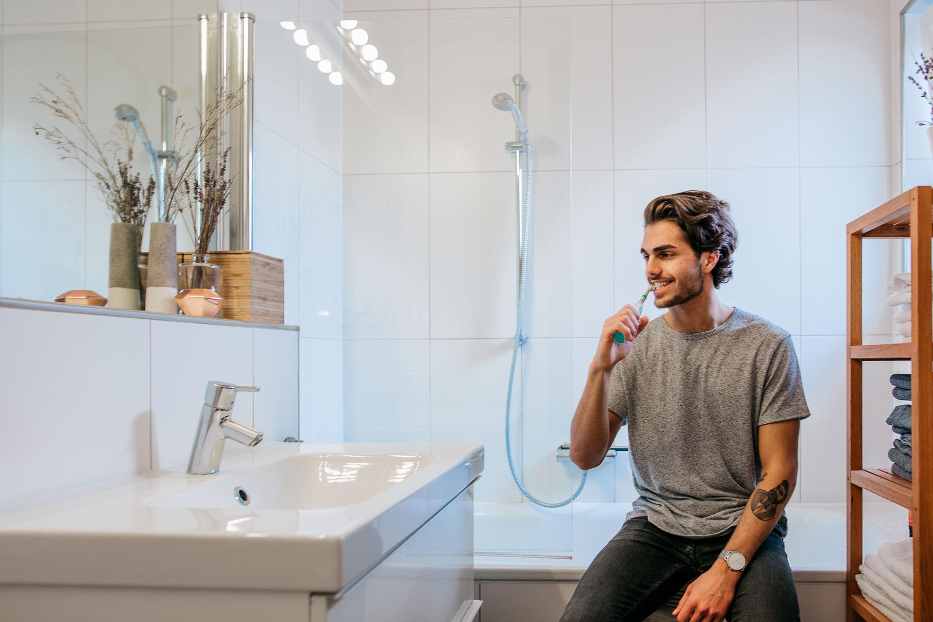 Social Media Fotografie für Happybrush: Ein junger Typ sitzt auf dem Badewannenrand und putzt mit einer Happybrush seine Zähne