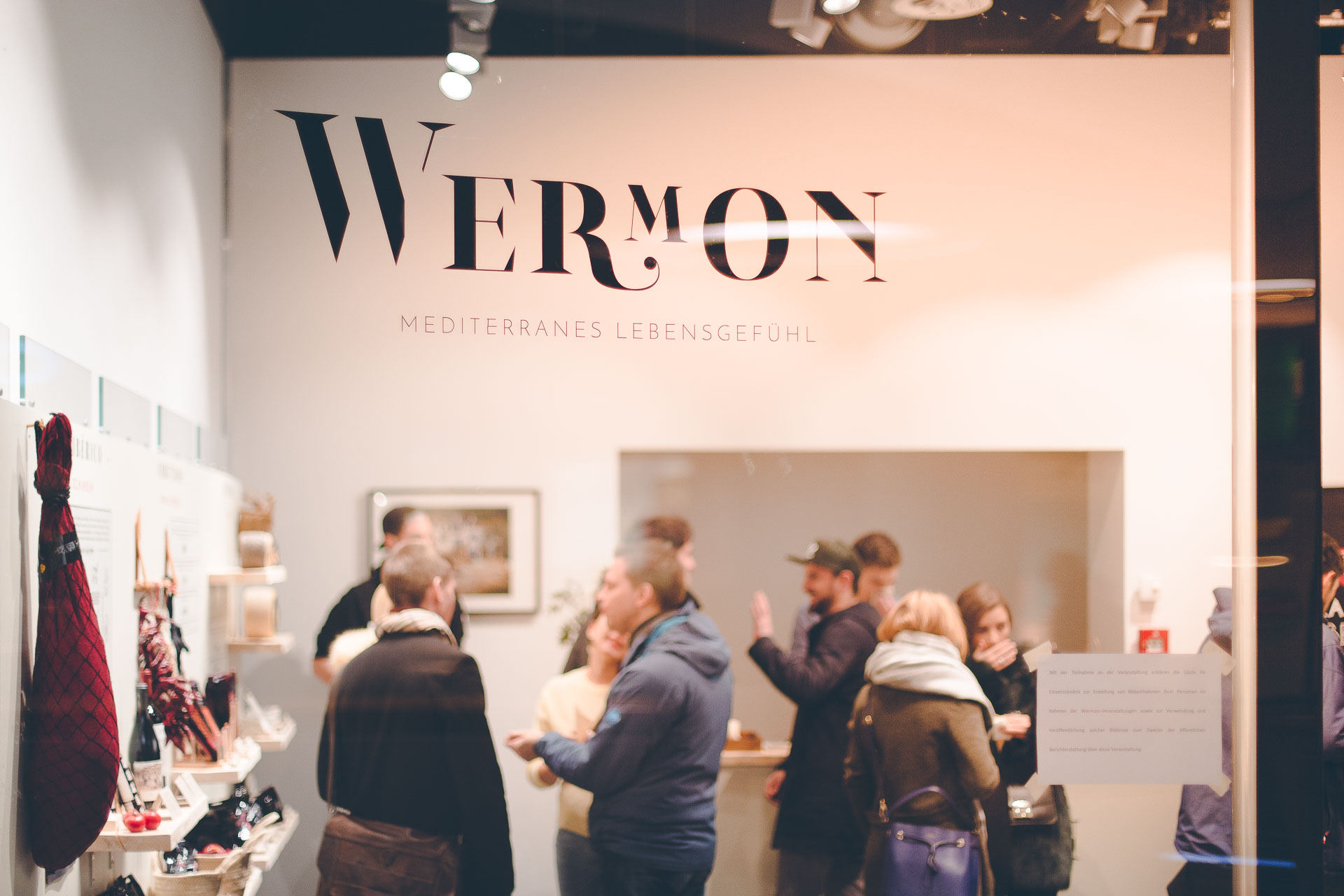 Das Wermon Logo an der Event Location auf einer Glasscheibe, dahinter verschwommen Besucher des Ladens in der Hofstatt