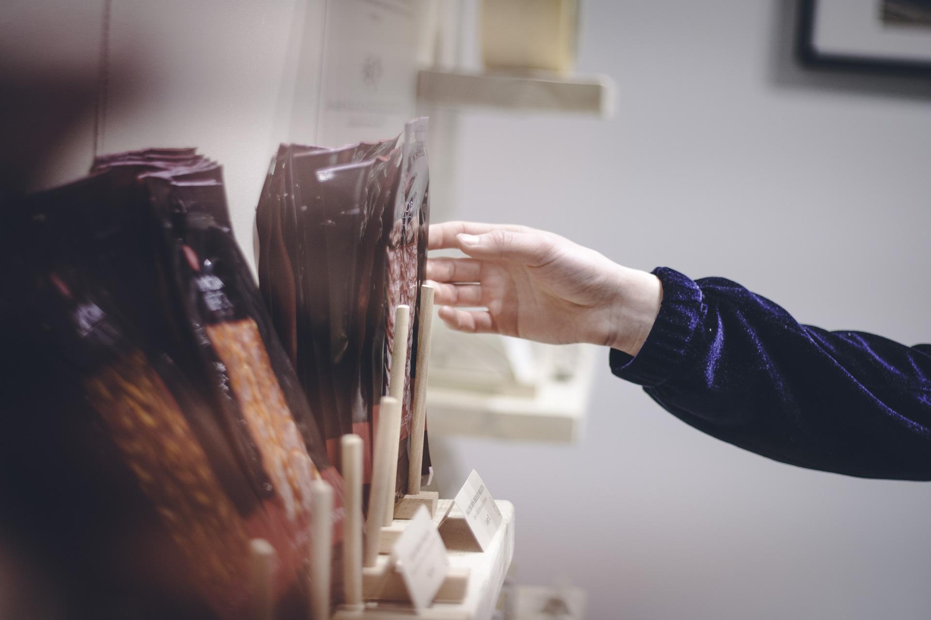 Hand einer Kundin greift nach Produkt