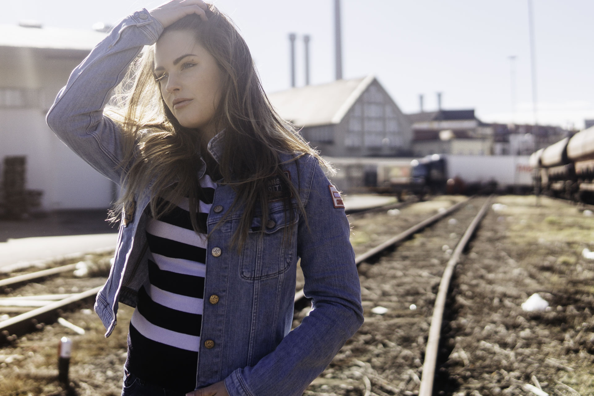 Münchener Model in Jeans Jacke steht in der Sonne auf Bahngleisen