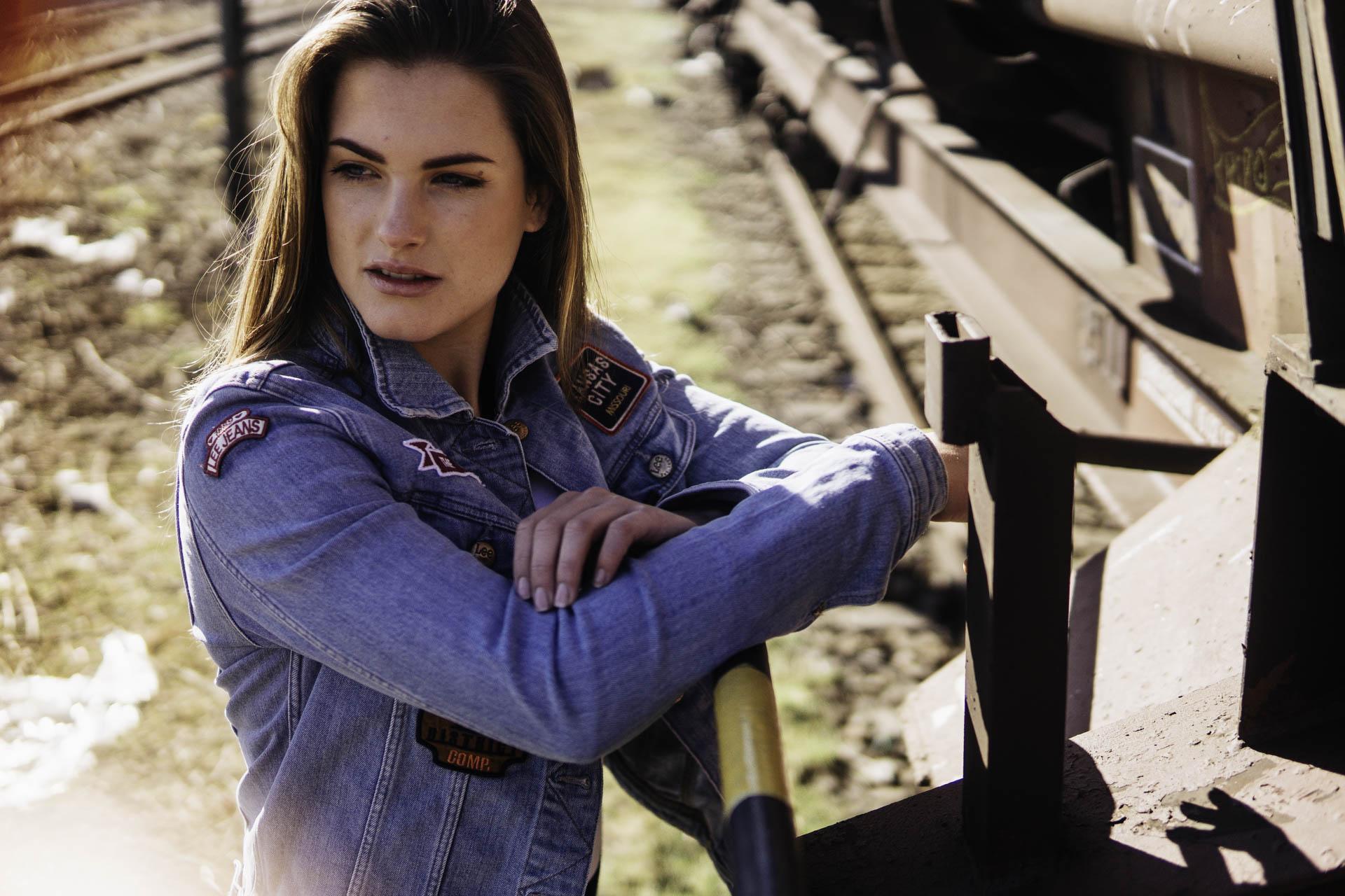 Münchener braunhaariges Model lehnt an Bahn Waggon in Jeansjacke