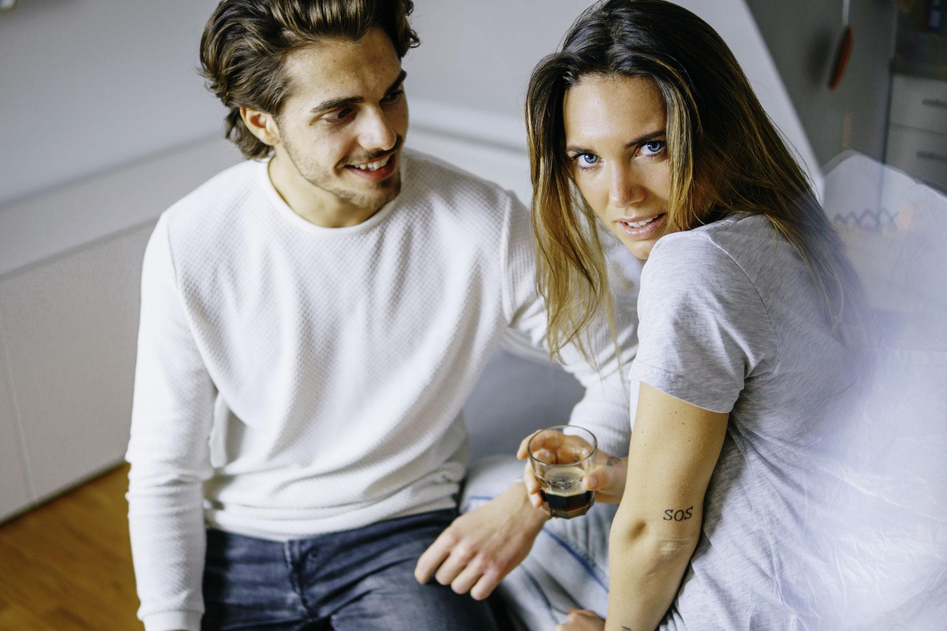Couple Shots mit einem jungen Paar am Küchentisch mit intensivem Blick und Kaffee