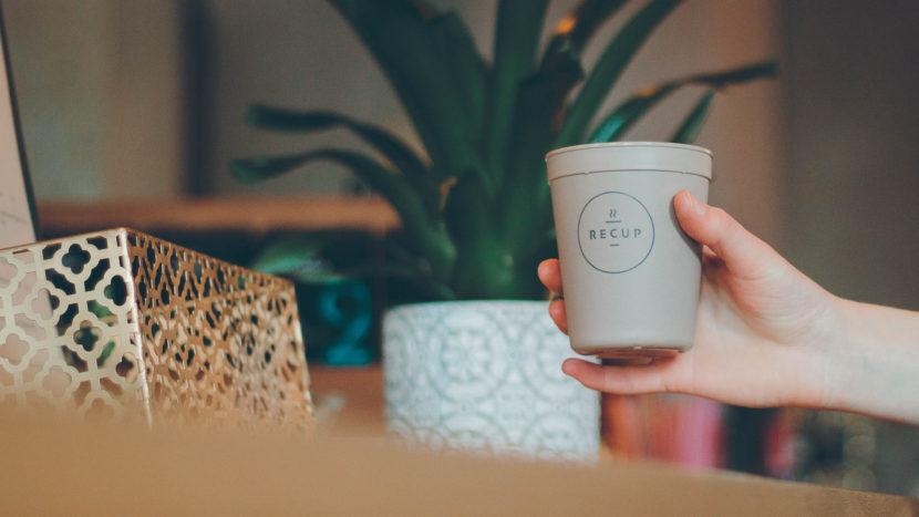 Nahaufnahme einer Kundenhand mit Recup an einem Kaffeetresen