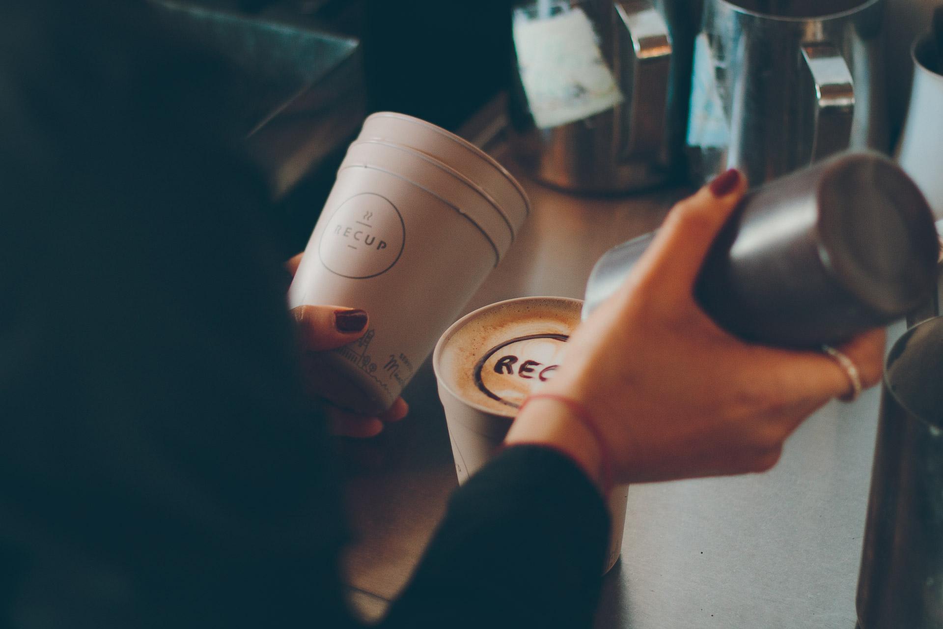 Eine Barista schreibt mit Schokoschrift Recup auf einen Kaffee