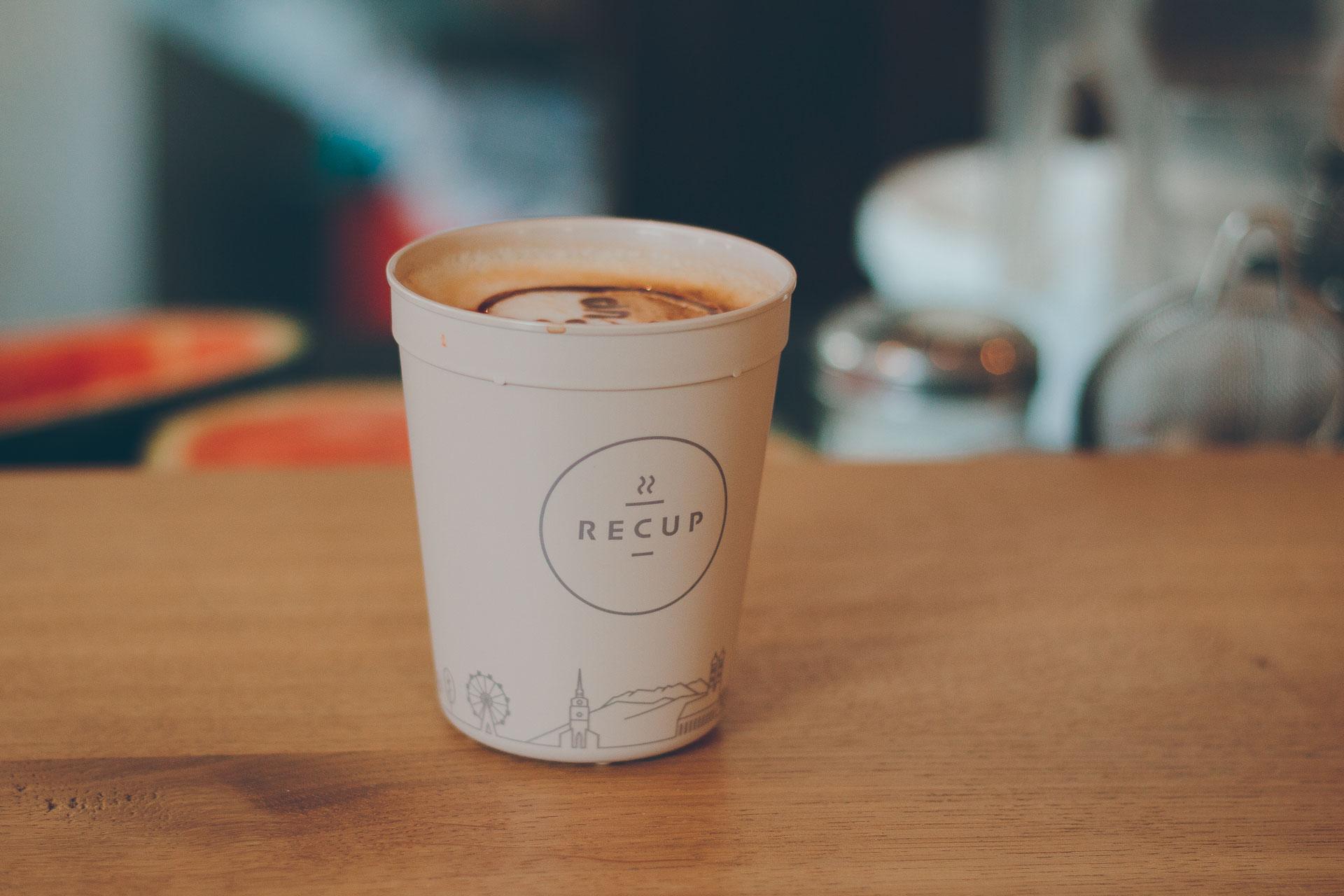 Nahaufnahme eines Recups mit Cappucino im Café