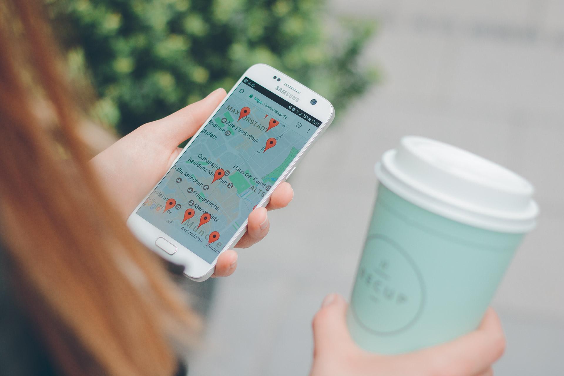 Social Media Foto eines Mädchens mit Recup und einer Karte von München auf dem Smartphone