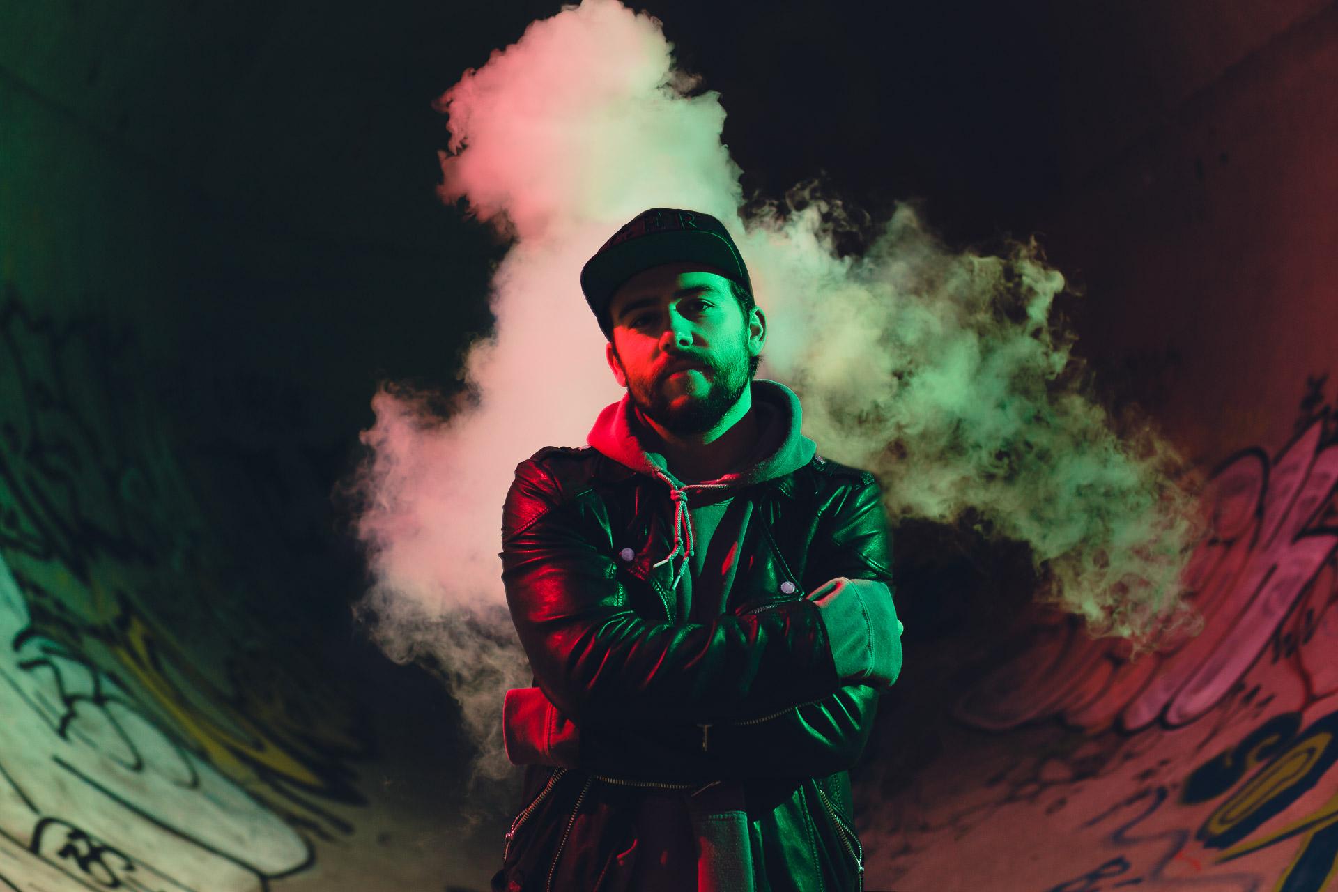 Neon Portrait von Ben Sammer mit grünem und rotem Blitz und Rauchwolke im Hintergrund im Hirschgarten Skatepark