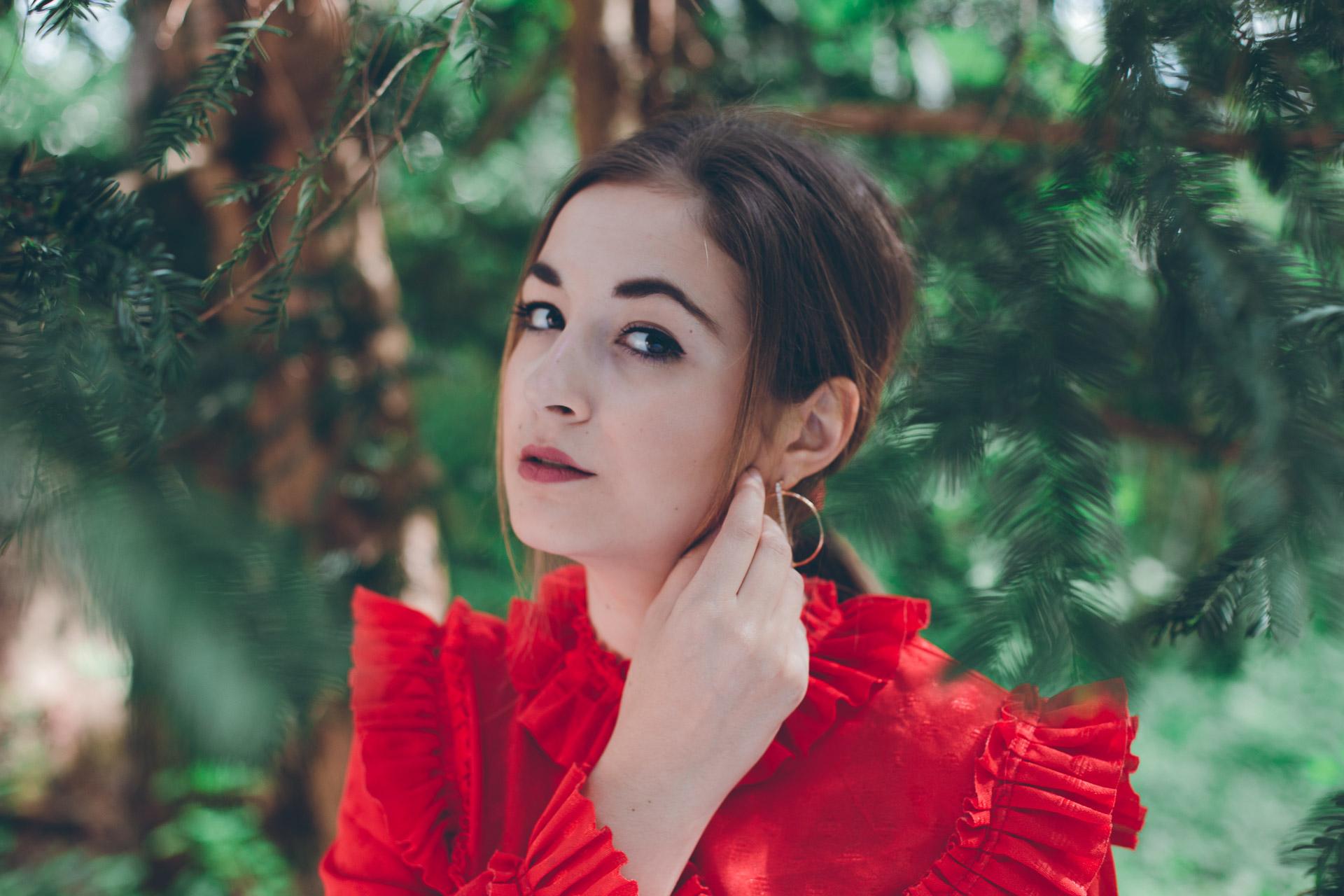 Portrait eines Mädchens mit roter Bluse, roten Lippen und weißer Haut inmitten des Walds