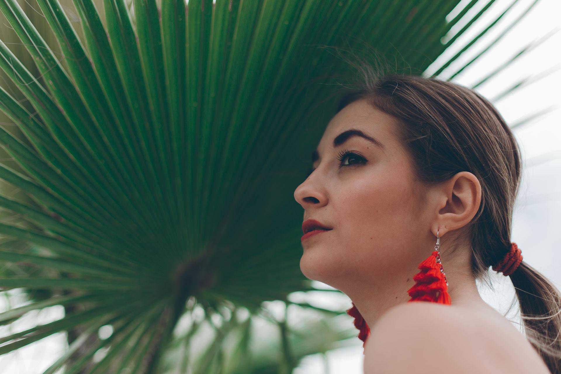 Stimmungsvolles Portrait eines Models unter einem Palmenblatt im botanischen Garten Nymphenburg