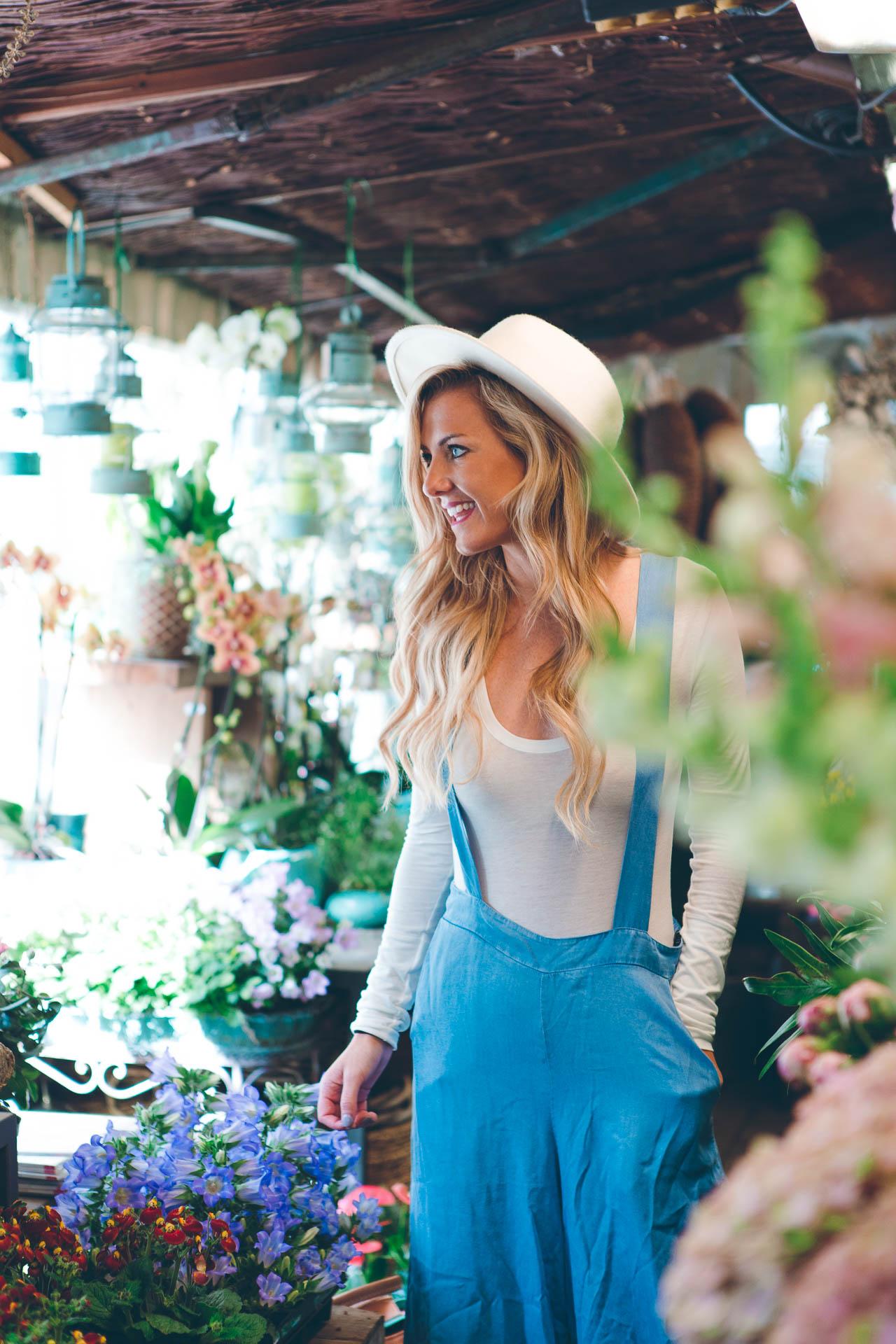 Blonde Frau bei einer Scrowl Photo Tour inmitten von Blumen am Viktualienmarkt München