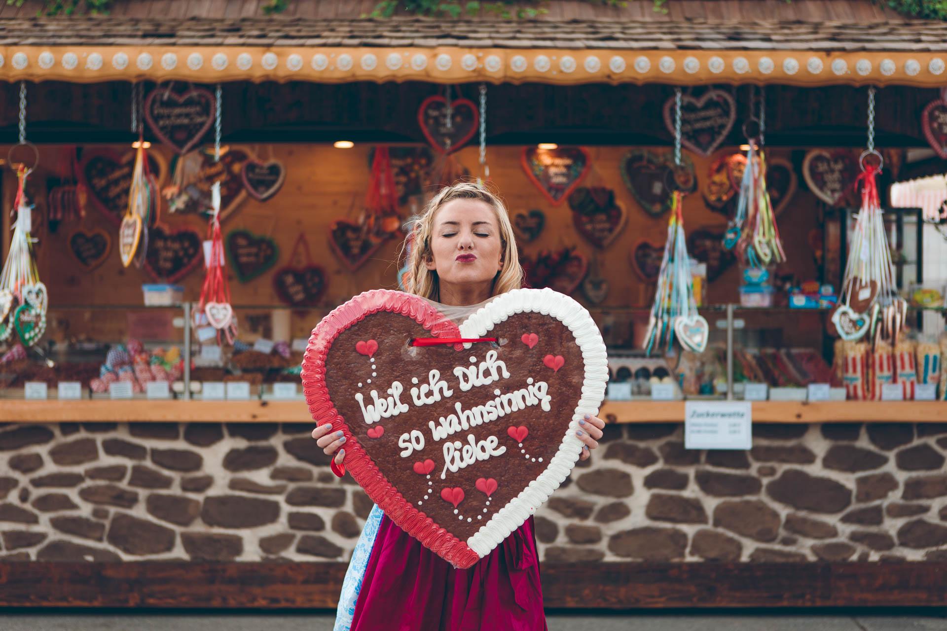 Blonde Frau im Dirndl mit riesigem Lebkuchenherz auf dem Frühlingsfest / Wiesn 2018