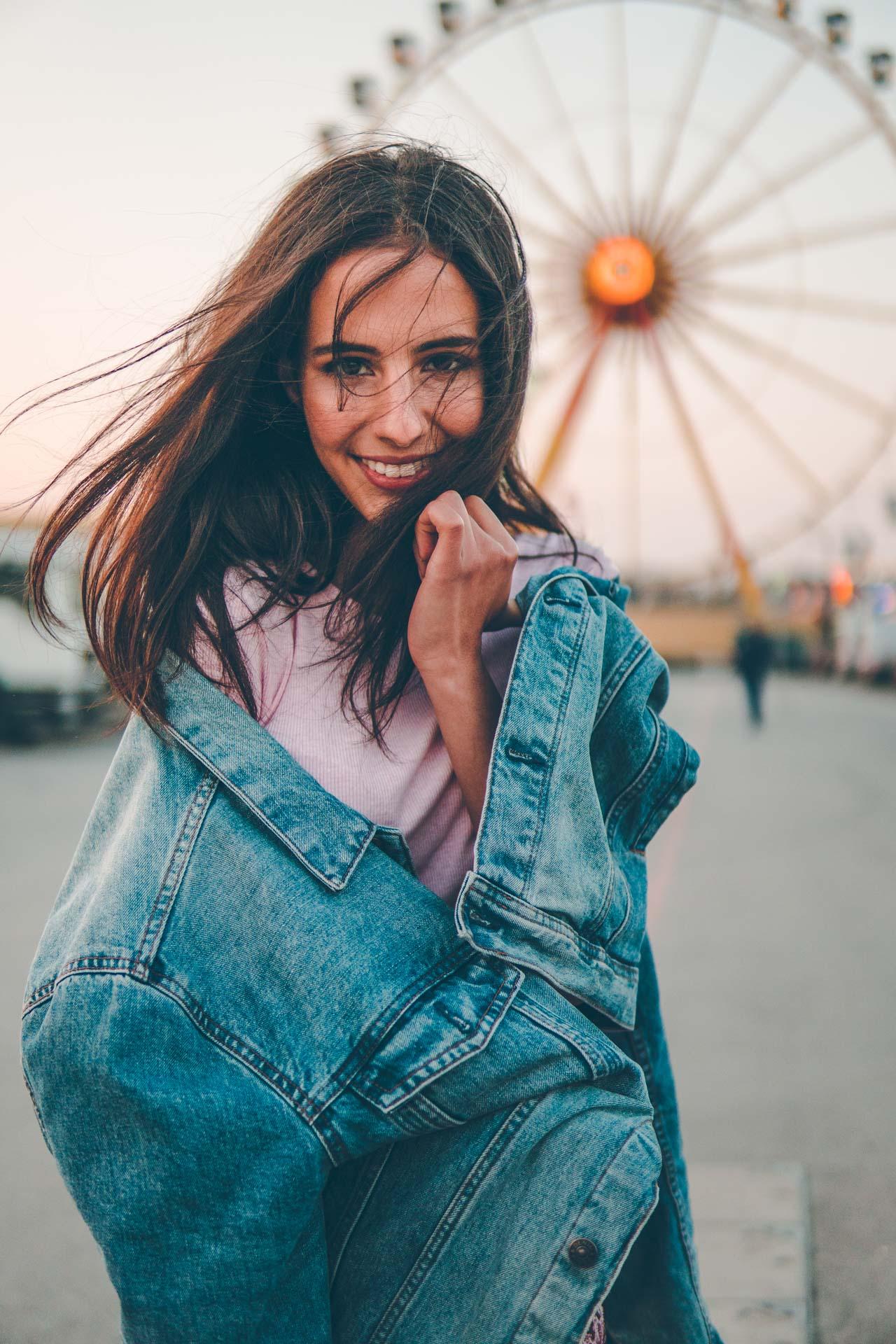 Lächelndes Mädchen mit Jeansjacke vor Reisenrad posiert für Lifestyle Shooting
