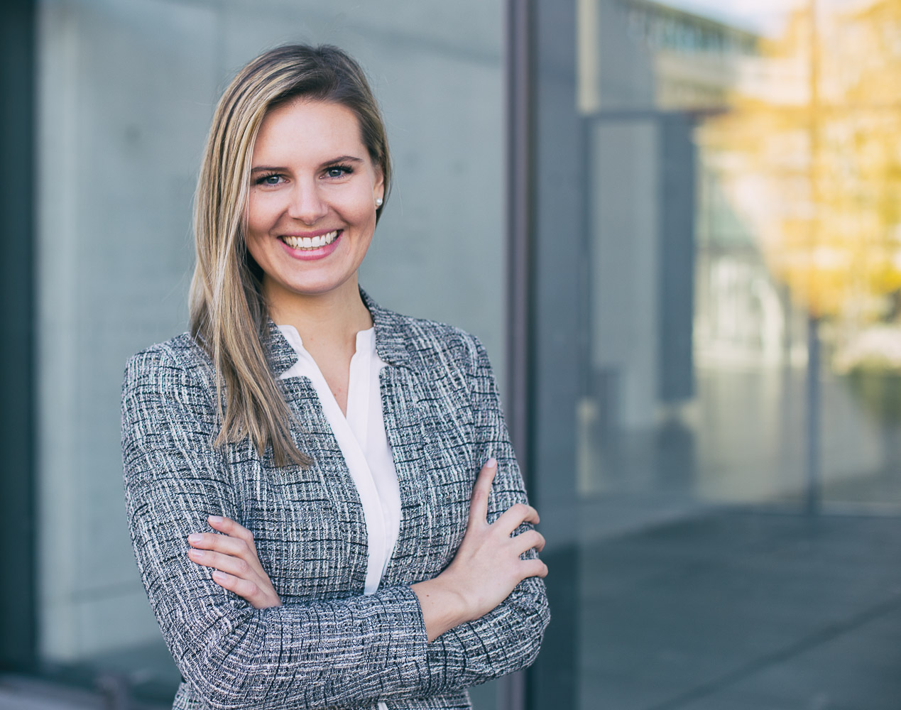 Eine junge Frau mit einem echten, natürlichen Lächeln auf einem Bewerbungsfoto von Scrowl München