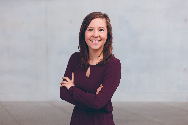 Freundliches Bewerbungsfoto einer jungen Mitarbeiterin im mitrubinrotem Kleid vor grauer Wand